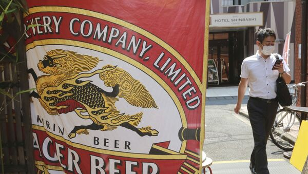 A man walks near an advertisement of a Kirin brand beer in Tokyo, Tuesday, Aug. 25, 2020. Australia's government announced on Tuesday it proposed to block Kirin Holdings Co.'s 45.6 billion yen ($430 million) sale of its Australian beverage unit to a Chinese company in a development likely to increase strain on Chinese-Australian relations. - Sputnik International