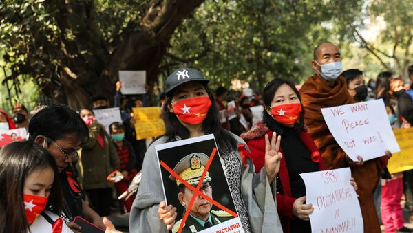 A woman holds a poster of Myanmar's army chief Min Aung Hlaing with his face crossed out during a protest, organised by Chin Refugee Committee, against the military coup in Myanmar, in New Delhi, India, February 5, 2021. REUTERS/Anushree Fadnavis - Sputnik International
