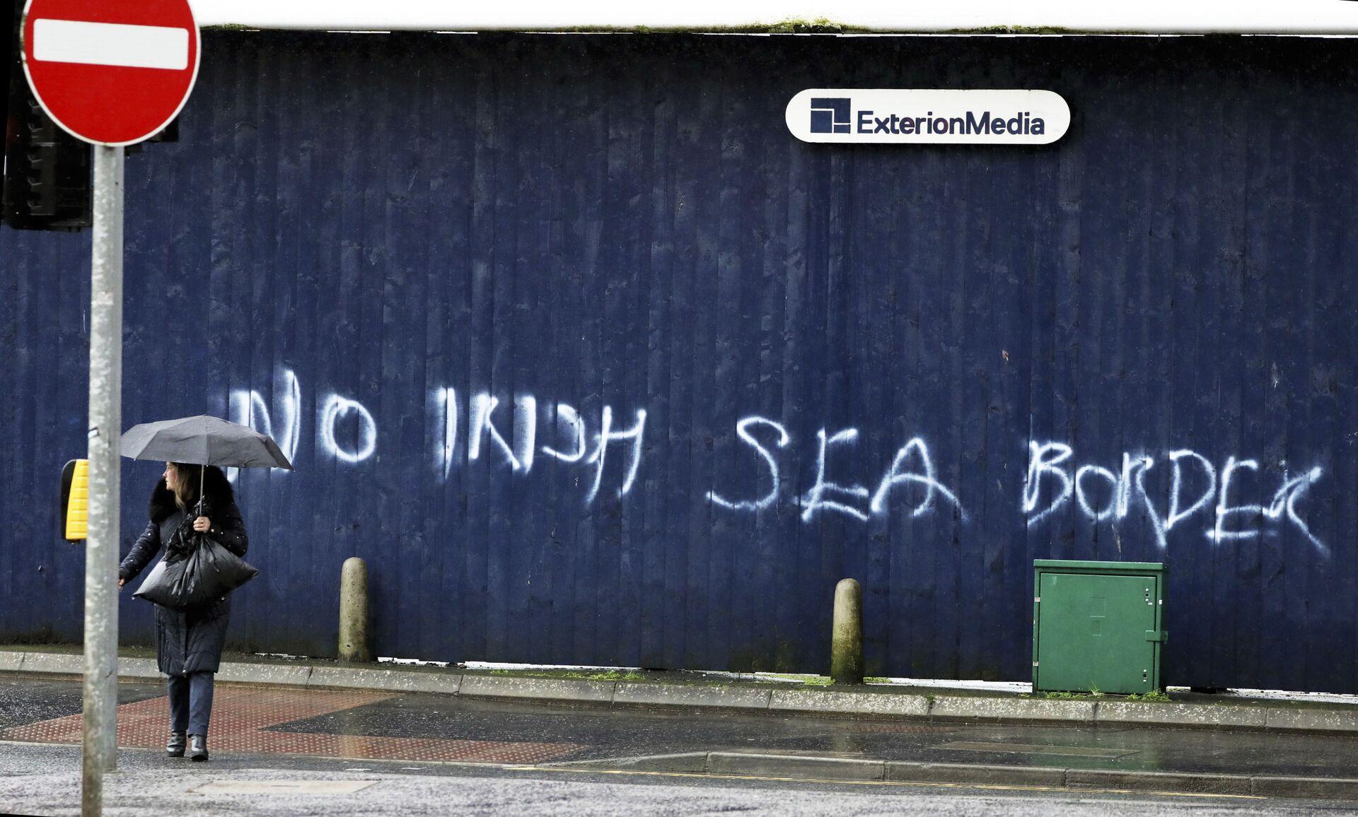 A woman walks past past graffiti with the words 'No Irish Sea Border' in Belfast city centre, Northern Ireland, Wednesday, Feb. 3, 2021 - Sputnik International, 1920, 13.10.2021