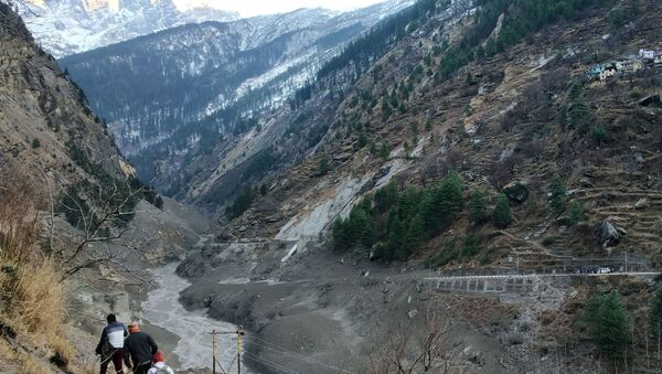 People walk past a destroyed dam after a Himalayan glacier broke and crashed into the dam at Raini Chak Lata village in Chamoli district, northern state of Uttarakhand, India, February 7, 2021. - Sputnik International