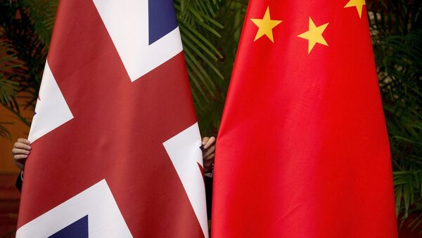 A worker adjusts British and China (R) national flags on display for a signing ceremony at the seventh UK-China Economic and Financial Dialogue Roundtable on Public-Private Partnerships at Diaoyutai State Guesthouse in Beijing, China September 21, 2015 - Sputnik International