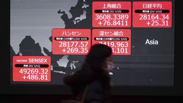 A woman wearing a face mask to help curb the spread of the coronavirus walks past an electronic stock board showing Japan's Nikkei 225 and other Asian indexes at a securities firm in Tokyo Tuesday, Jan. 12, 2021. - Sputnik International