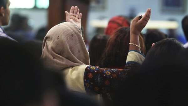 In this Sunday, Jan. 20, 2019 photo, a woman prays during Mass at St. Mary's Catholic Church in Dubai, United Arab Emirates. The Catholic Church's parishioners in the UAE come from around the world and will offer an international welcome to Pope Francis Feb. 3 through Feb. 5, that marks the first ever papal visit to the Arabian Peninsula, the birthplace of Islam. The Catholic Church believes there are some 1 million Catholics in the UAE today. - Sputnik International