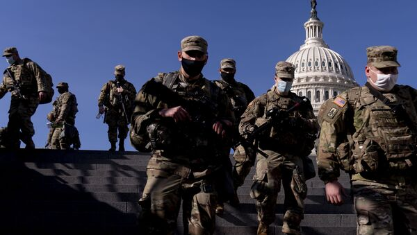 Members of the National Guard walk past the dome of the Capitol Building on Capitol Hill in Washington, Thursday, Jan. 14, 2021 - Sputnik International
