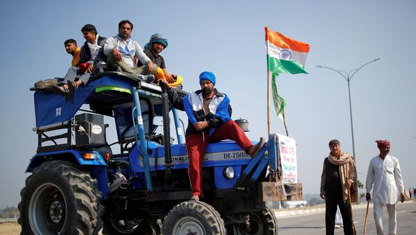 Farmers stand atop a tractor as they take part in a three-hour chakka jam, or road blockade, as part of protests against farm laws on a highway on the outskirts of New Delhi - Sputnik International