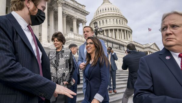 Rep. Lauren Boebert, R-Colo., centre, smiles after joining other freshman Republican House members for a group photo at the Capitol in Washington, Monday, 4 January 2021. Rep. Jerry Carl, R-Ala., is at right.  - Sputnik International