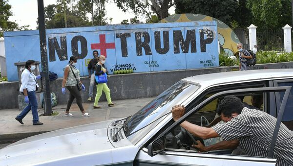 A man pushes his car that ran out of gas as people wearing protective face masks as a precaution against the spread of the new coronavirus, walk past a mural with a message that reads in Spanish:  No more Trump in Caracas, Venezuela, Sunday, Nov. 8, 2020. Venezuelan President Nicolas Maduro has sent a congratulatory message to U.S. President-elect Joe Biden who won the U.S. presidential election, defeating incumbent Donald Trump. - Sputnik International