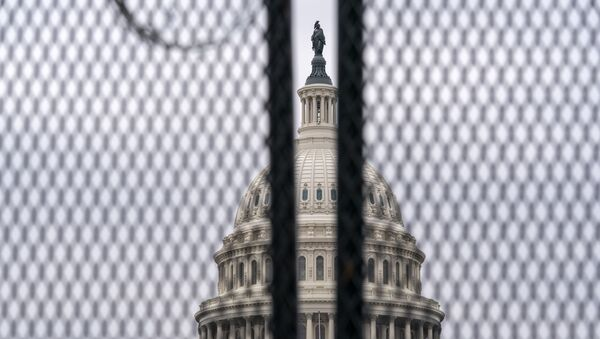 The U.S. Capitol is seen through a fence with barbed wire during the second impeachment trial of former President Donald Trump in Washington, Friday, 12 February 2021.  - Sputnik International