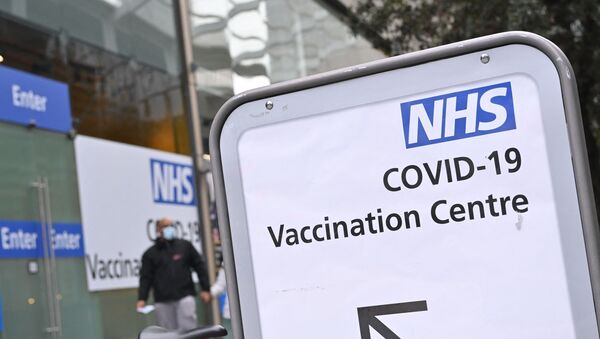 A pedestrian walks past an NHS Covid-19 vaccination centre in Westfield Stratford City shopping centre in east London on February 6, 2021 as Britain's largest ever vaccination programme continues.  - Sputnik International