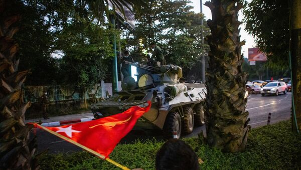 A man waves a flag next to an armoured vehicle during a protest against the military coup, in Yangon, Myanmar, February 14, 2021.  - Sputnik International