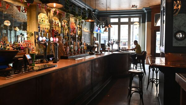 A single customer sits at the bar in a near-empty pub in central London on March 17, 2020 after the UK government announced stringent social distancing advice including avoiding pubs and restaurants as a measure to kerb the spread of novel coronavirus COVID-19 - Sputnik International