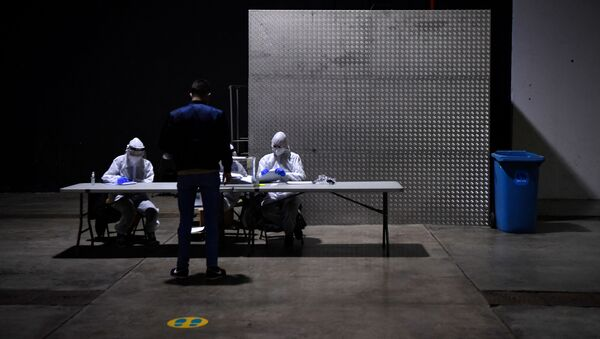 Officials wear Personal Protective Equipment (PPE) as a person casts his ballot during the voting period assigned for those infected with COVID-19 at a polling station in L'Hospitalet de Llobregat during regional elections in Catalonia on February 14, 2021.  - Sputnik International