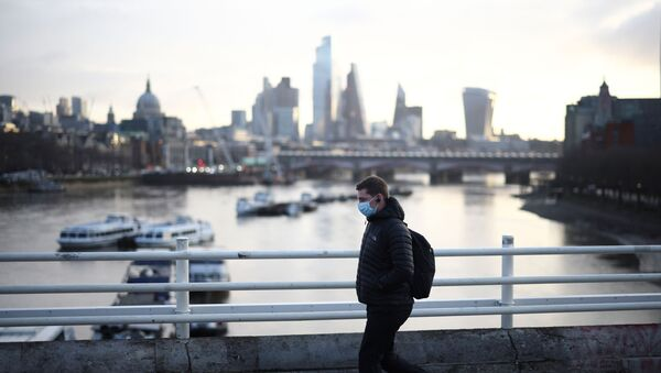 A man wearing a protective face mask walks across Waterloo Bridge, amid the coronavirus disease (COVID-19) outbreak in London, Britain, January 29, 2021. - Sputnik International