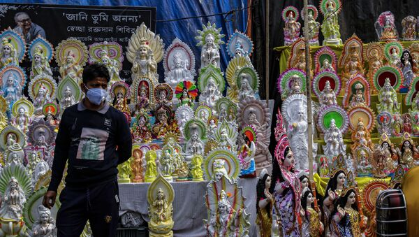 An Indian vendor wearing a face mask as a precaution against the coronavirus awaits customers as he sells clay images of Saraswati, the Hindu goddess of wisdom, ahead of the Basant Panchami festival in Kolkata, India, Sunday, 14 February 2021. The festival, which will be celebrated on 16 February, marks the arrival of spring. - Sputnik International