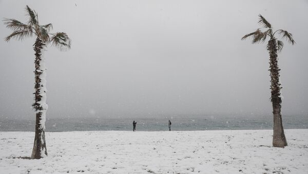 People take photos on a snow-covered beach during heavy snowfall in the suburb of Glyfada, in Athens, Greece, February 16, 2021. - Sputnik International