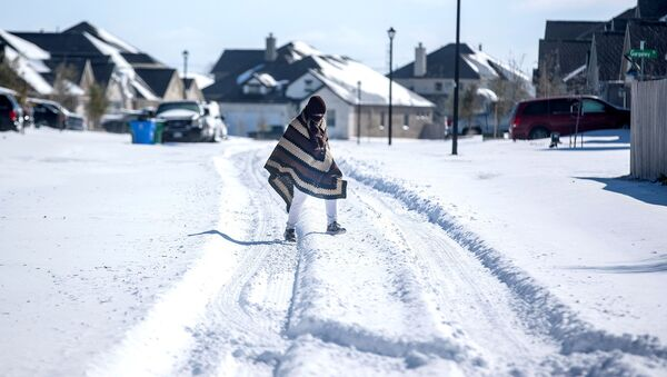A man walks to his friend's home in a neighbourhood without electricity as snow covers the BlackHawk neighborhood in Pflugerville, Texas, U.S. February 15, 2021. Picture taken February 15, 2021 - Sputnik International