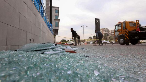 A worker cleans shattered glass on February 16, 2021 outside a damaged shop following a rocket attack the previous night in Arbil, the capital of the northern Iraqi Kurdish autonomous region - Sputnik International