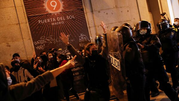 A person raises the hands in front of police officers as supporters of Catalan rapper Pablo Hasel protest against his arrest in Madrid, Spain, February 17, 2021. - Sputnik International