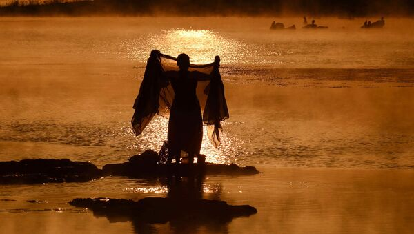 An Indian woman washes a sari in the Narmada River at sunrise on a foggy winter morning in Jabalpur in Madhya Pradesh state on January 2, 2019 - Sputnik International