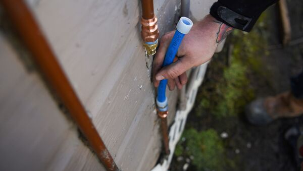 Tyler Riese, a plumber, fixes a pipe, which burst after freezing, following an unprecedented winter storm in Houston, Texas, U.S., February 19, 2021.  - Sputnik International