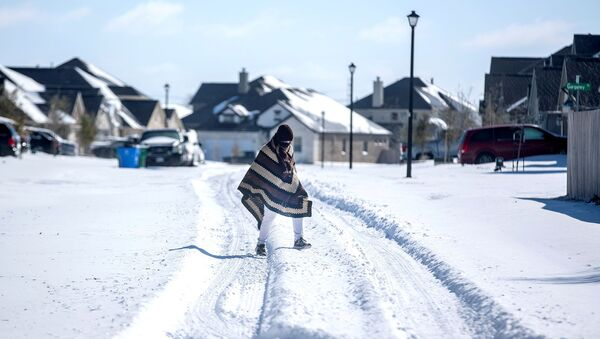 A man walks to his friend's home in a neighbourhood without electricity as snow covers the BlackHawk neighborhood in Pflugerville, Texas, U.S. February 15, 2021. Picture taken February 15, 2021.  - Sputnik International