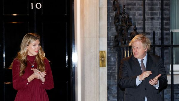 Britain's Prime Minister Boris Johnson and partner Carrie Symonds applaud outside 10 Downing Street during a national clap for late Captain Sir Tom Moore and NHS workers, amidst the coronavirus disease (COVID-19) outbreak, in London, Britain, 3 February 2021.  - Sputnik International