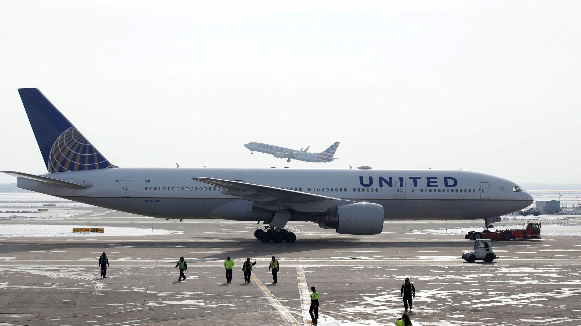 A United Airlines Boeing 777-200ER  plane is towed as an American Airlines Boeing 737 plane departs from O'Hare International Airport in Chicago, Illinois, U.S. Nov. 30, 2018.  - Sputnik International, 1920, 21.09.2021