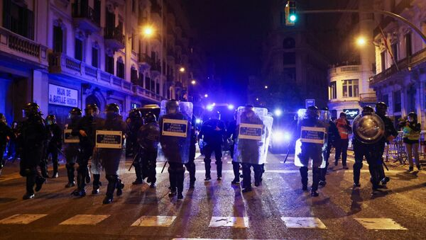 Police officers walk during a protest in support of rap singer Pablo Hasel after he was given a jail sentence on charges of glorifying terrorism and insulting royalty in his songs, in Barcelona, Spain, February 21, 2021. - Sputnik International