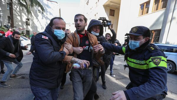 Georgian law enforcement officers detain a man during a demonstration held by opposition supporters near the parliament building in Tbilisi, Georgia 22 February 2021.  - Sputnik International