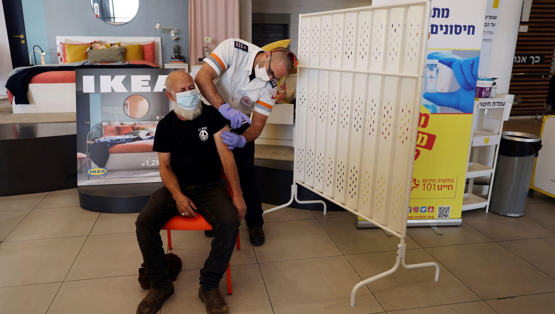 A man receives a vaccination against the coronavirus disease (COVID-19) in an IKEA store in Rishon Lezion, Israel February 22, 2021.  - Sputnik International, 1920, 26.08.2021