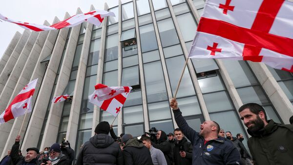 Opposition supporters wave flags following the announcement of Georgian Prime Minister Giorgi Gakharia's resignation outside the headquarters of the United National Movement (UNM) party in Tbilisi, Georgia February 18, 2021. - Sputnik International