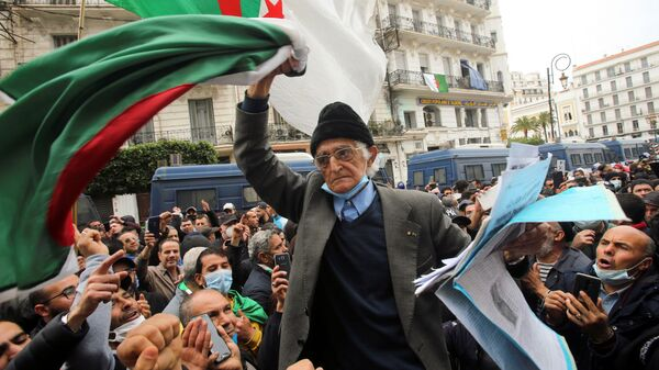 A demonstrator carries a national flag during a protest to mark the second anniversary of a mass protest movement demanding political change, in Algiers, Algeria February 22, 2021 - Sputnik International