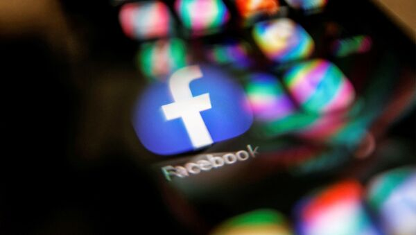 The Facebook logo displayed on a mobile phone is seen through a magnifying glass in this picture illustration taken February 9, 2021 - Sputnik International