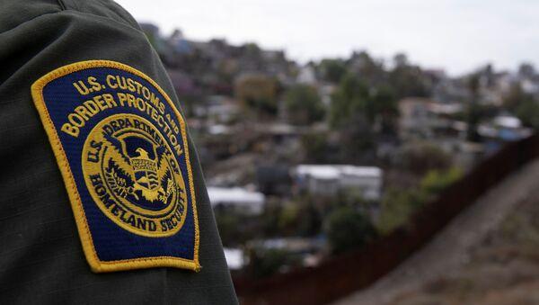 A U.S. border patrol agent looks out over Tijuana, Mexico from the U.S. Mexico border wall in San Diego, California, U.S., February 2, 2021 - Sputnik International