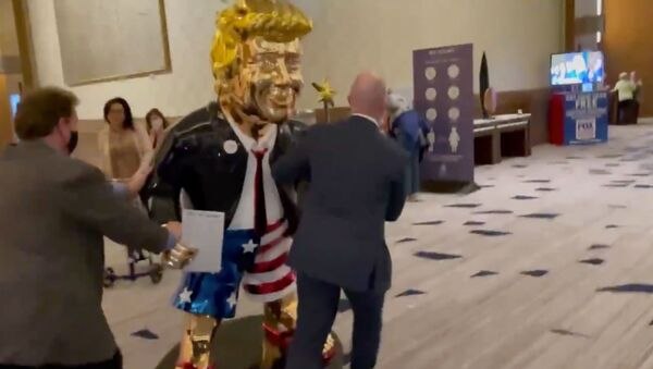 Screenshot captures golden statue of former US President Donald Trump being wheeled toward an event associated with the annual Conservative Police Action Conference. - Sputnik International
