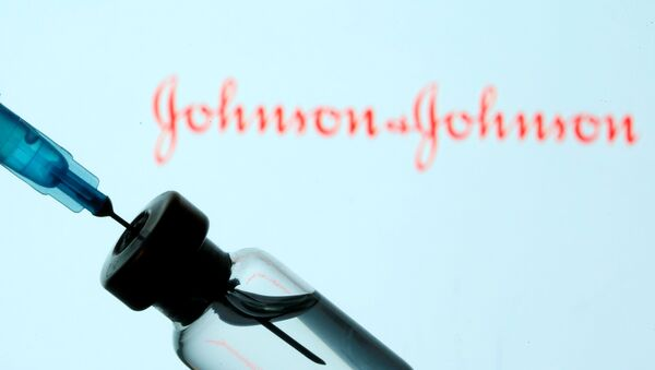 A vial and sryinge are seen in front of a displayed Johnson&Johnson logo in this illustration taken January 11, 2021 - Sputnik International