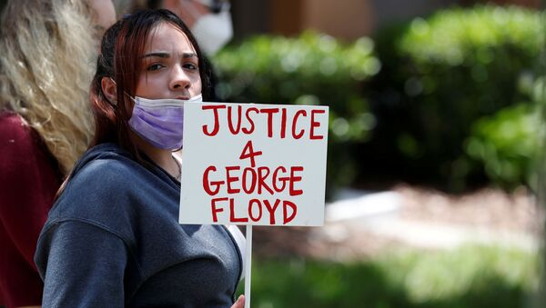 A protester holds a sign outside the Florida home of former Minneapolis police officer Derek Chauvin, who was recorded with his knee on the neck of African-American man George Floyd - Sputnik International