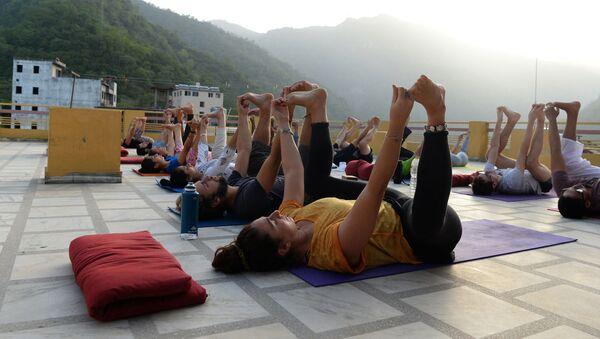 This picture taken on June 19, 2018, shows people practising yoga on a terrace at the Anand Prakash yoga ashram in Rishikesh in India's Uttarakhand state - Sputnik International