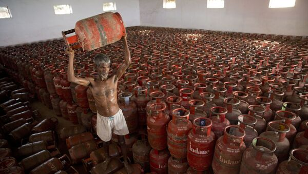 An Indian laborer sorts Liquid Petroleum Gas (LPG) cylinders used for cooking at a warehouse after downloading them from  a truck in Allahabad, India, Monday, Aug.1, 2016 - Sputnik International