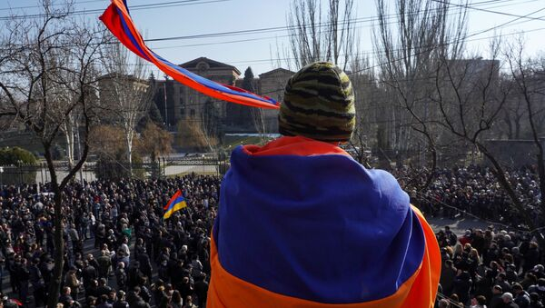An opposition supporter wrapped in a national flag attends a rally to demand the resignation of Armenian Prime Minister Nikol Pashinyan, in Yerevan, Armenia February 27, 2021 - Sputnik International