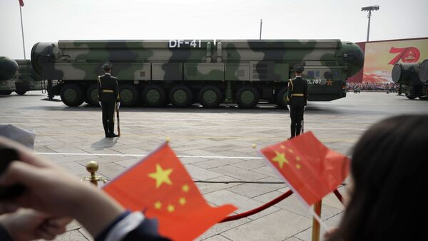 FILE - In this Oct. 1, 2019, file photo spectators wave Chinese flags as military vehicles carrying DF-41 ballistic missiles roll during a parade to commemorate the 70th anniversary of the founding of Communist China in Beijing. Trucks carrying weapons including a nuclear-armed missile designed to evade U.S. defenses rumbled through Beijing as the Communist Party celebrated its 70th anniversary in power - Sputnik International