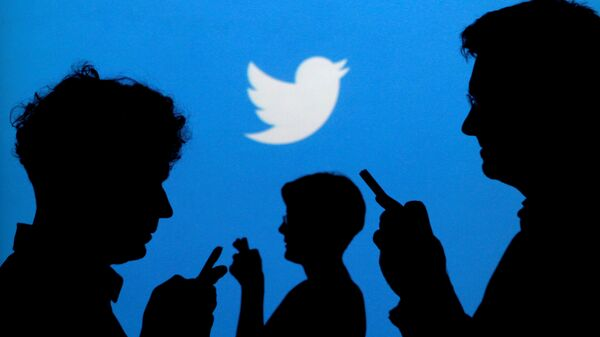 People holding mobile phones are silhouetted against a backdrop projected with the Twitter logo in this illustration picture taken September 27, 2013 - Sputnik International