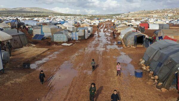 Syrian refugees walk through a camp for displaced muddied by recent rains near the village of Kafr Aruq , in Idlib province, Syria, Thursday, Jan. 28, 2021. - Sputnik International