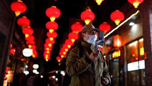 A man wearing a face mask following an outbreak of the coronavirus disease (COVID-19) uses his phone while walking near the Qianmen street ahead of Lunar New Year celebrations, in Beijing, China February 10, 2021 - Sputnik International