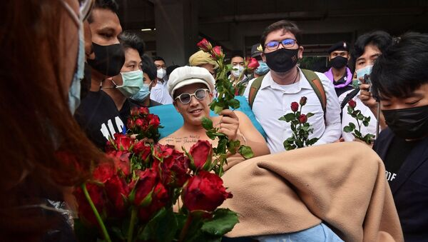 Anti-government blues musician Ammy The Bottom Blues receives flowers as he is wheeled on a hospital bed outside the Office of the Attorney General in Bangkok on February 17, 2021, before the state prosecutor decided whether to indict 18 activists on charges including sedition and lese majeste related to anti-government protests in 2020. - Sputnik International
