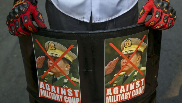 An anti-coup protester displays defaced images of Commander in chief, Senior Gen. Min Aung Hlaing in Mandalay, Myanmar, Wednesday, March 3, 2021. - Sputnik International