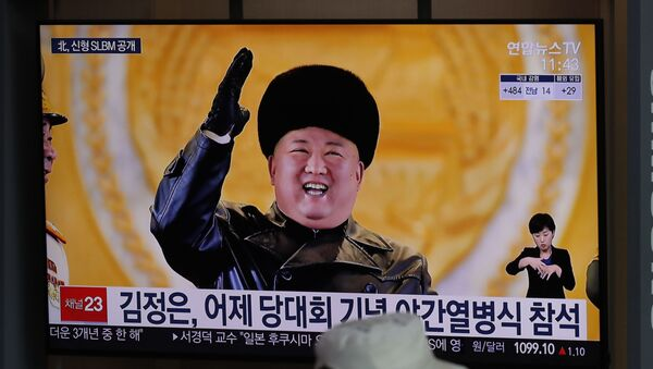A man wearing a face mask sits in front of a TV screen showing North Korean leader Kim Jong Un, at the Seoul Railway Station in Seoul, South Korea, Friday, Jan. 15, 2021 - Sputnik International