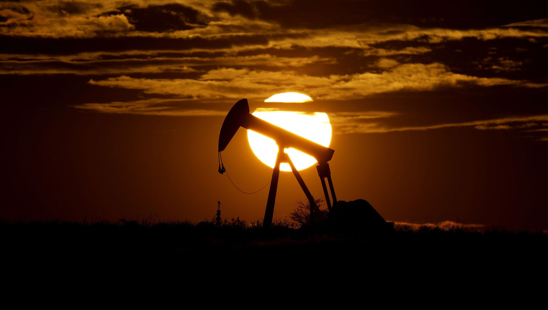 In this Wednesday, April 8, 2020, file photo, the sun sets behind an idle pump jack near Karnes City, Texas. Demand for oil continues to fall due to the new coronavirus outbreak. - Sputnik International, 1920, 16.08.2021