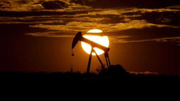 In this Wednesday, April 8, 2020, file photo, the sun sets behind an idle pump jack near Karnes City, Texas. Demand for oil continues to fall due to the new coronavirus outbreak. - Sputnik International