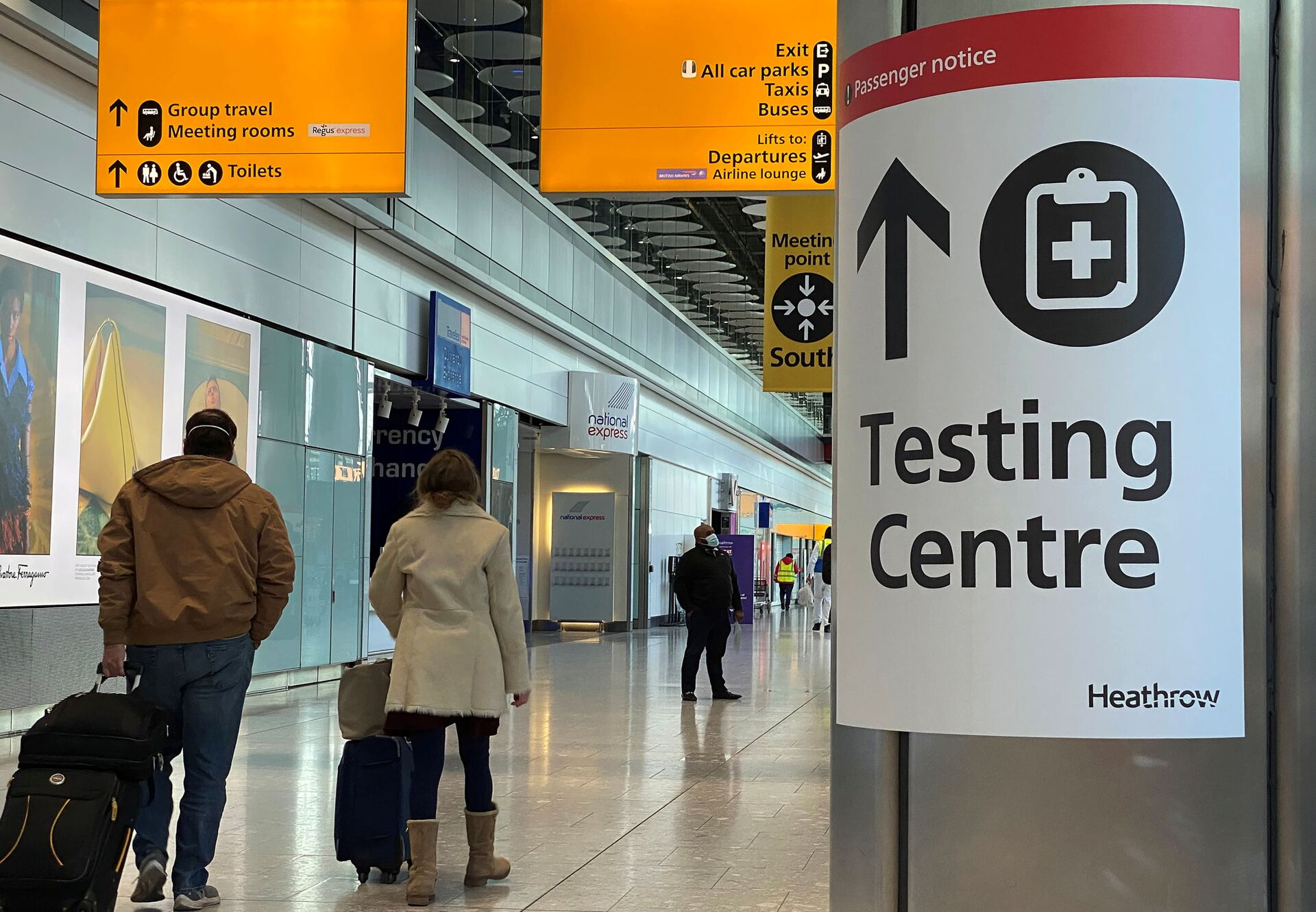 Travellers pass a sign for a COVID-19 test centre at Heathrow Airport, London, Britain, February 13, 2021. - Sputnik International, 1920, 07.09.2021